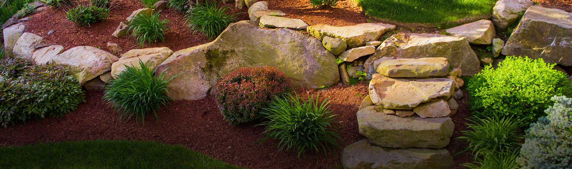 Landscaped flower bed with red mulch